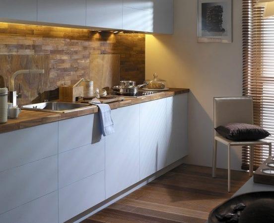 Белоснежная кухонная мебель с деревянной столешницей в медовых тонах