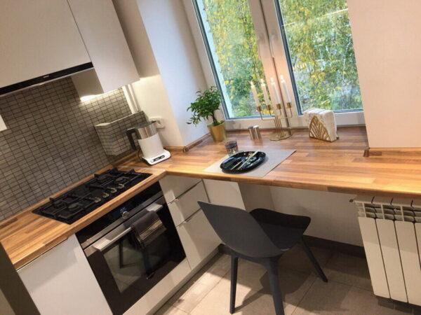 Дизайн кухонного гарнитура со столешницей под окном