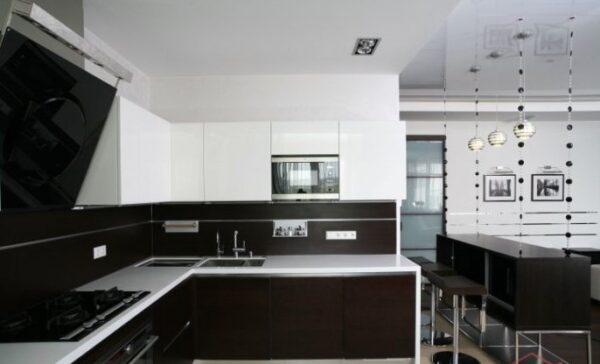 Угловая кухня в черно-белом оформлении, гладкий матовый гарнитур и белые обои в стиле минимализм